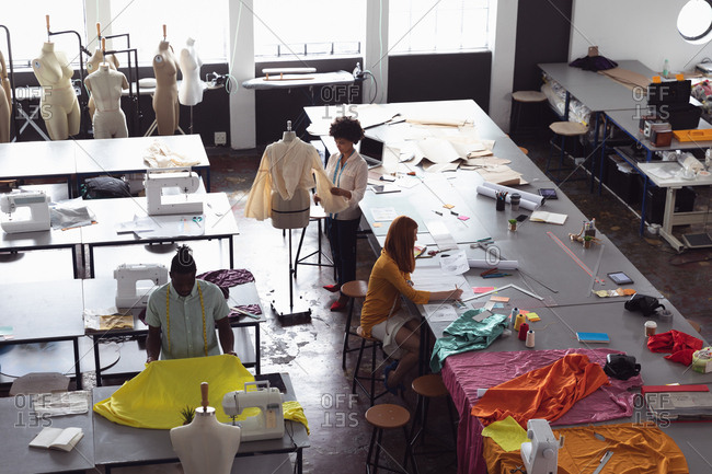High angle view of a diverse group of fashion students working on designs in a studio at fashion college