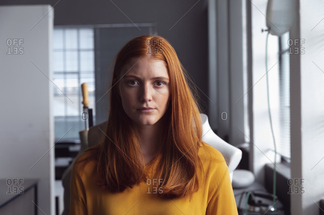 Front view of a young Caucasian female fashion student looking straight to camera in a studio at fashion college