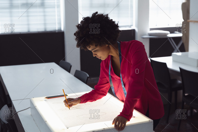 Side view of a young mixed race female fashion student working on a design drawing on a lightbox in a studio at fashion college