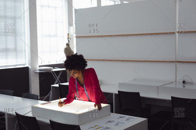 Front view of a young mixed race female fashion student working on a design drawing on a lightbox in a studio at fashion college