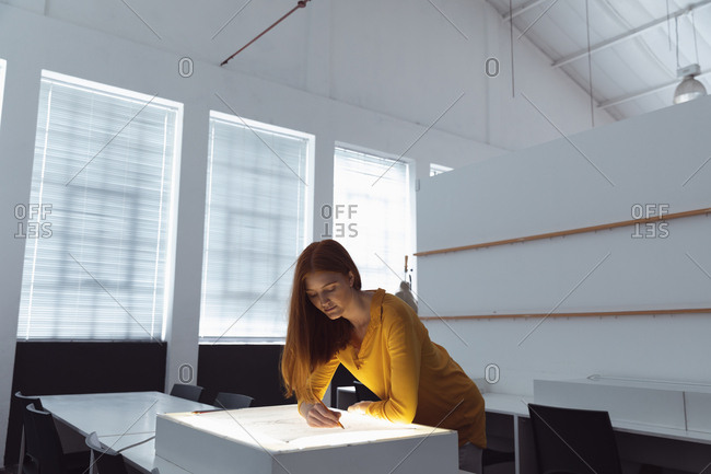 Front view of a young Caucasian female fashion student working on a design drawing on a lightbox in a studio at fashion college
