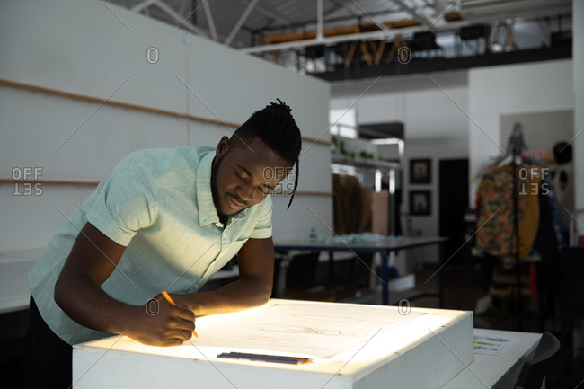 Side view of a young African American male fashion student working on a design drawing on a lightbox in a studio at fashion college