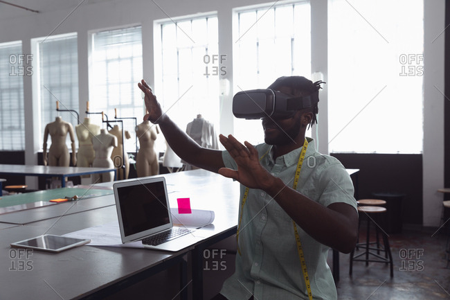 Front view of a young African American male fashion student with his hands raised using a VR headset in a studio at fashion college with a computer and a tablet computer on the table in front of him, and mannequins in the background