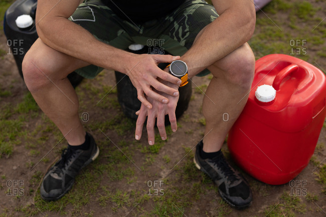 Front view low section of a young Caucasian man sitting and checking his watch at an outdoor gym before a bootcamp training session