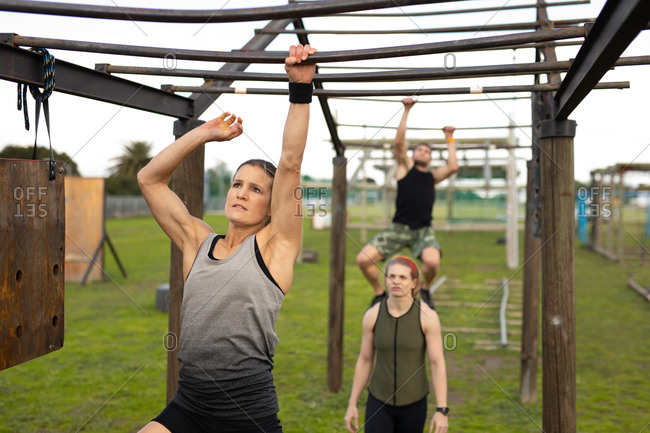 Front view of a young Caucasian woman hanging from monkey bars at an outdoor gym during a bootcamp training session with two other participants in the background