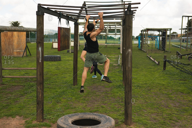 Rear view of a young Caucasian man hanging from monkey bars at an outdoor gym during a bootcamp training session, with other participants in the background