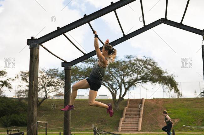 Side view of a young Caucasian woman hanging from monkey bars at an outdoor gym during a bootcamp training session, with another participant in the background