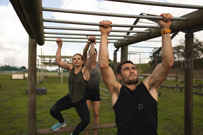 Front view of a young Caucasian man and a young Caucasian woman hanging from monkey bars at an outdoor gym during a bootcamp training session, with another participant also hanging from the bars in the background