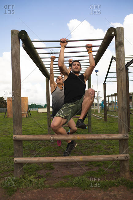 Front view of a young Caucasian man and a young Caucasian woman hanging from monkey bars at an outdoor gym during a bootcamp training session