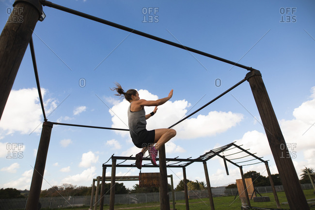 Side view of a young Caucasian woman in mid air swinging between bars on a frame at an outdoor gym during a bootcamp training session