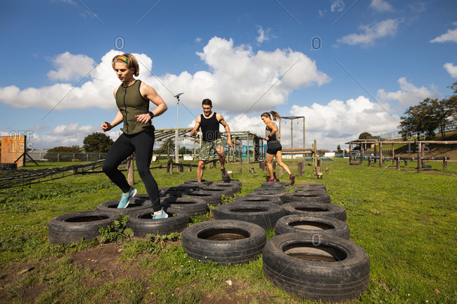 Front view of two young Caucasian women and a young Caucasian man stepping through tires at an outdoor gym during a bootcamp training session