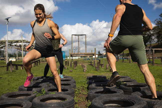 Front view of a young Caucasian woman and rear view of a young Caucasian man stepping through tires at an outdoor gym during a bootcamp training session, with another participant in the background