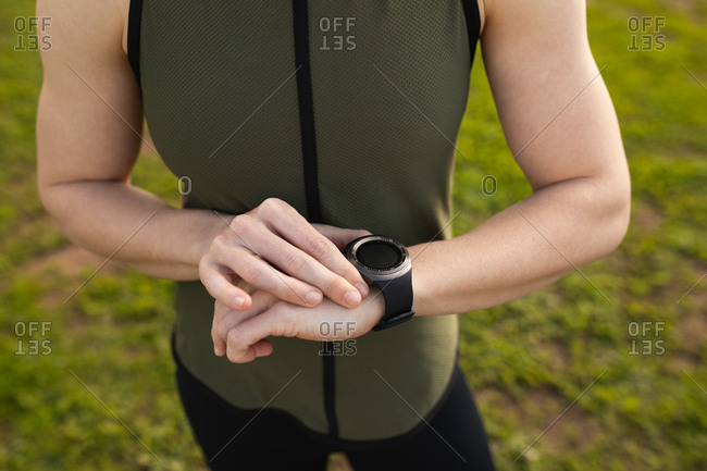 Front view mid section of a young Caucasian woman standing and checking her watch at an outdoor gym during a bootcamp training session