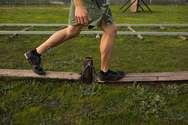 Side view low section of a young Caucasian man walking along wooden poles at an outdoor gym during a bootcamp training session
