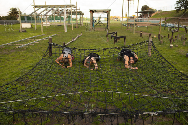 Front view of two young Caucasian women and a young Caucasian man crawling under a net at an outdoor gym during a bootcamp training session