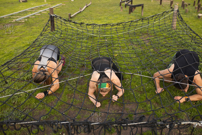 Front view close up of two young Caucasian women and a young Caucasian man crawling under a net at an outdoor gym during a bootcamp training session