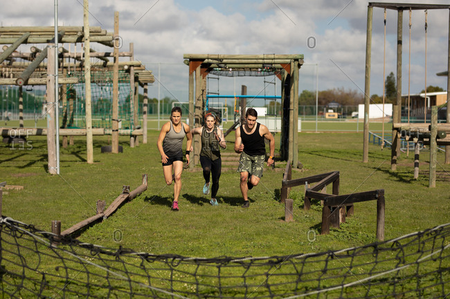 Front view of two young Caucasian women and a young Caucasian man running between obstacles at an outdoor gym during a bootcamp training session