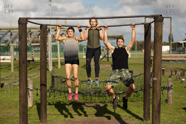 Front view of two young Caucasian women and a young Caucasian man doing pull ups hanging from a frame at an outdoor gym during a bootcamp training session