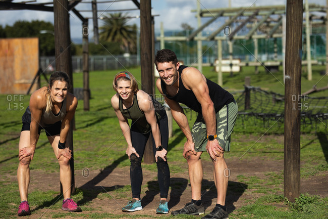 Front view of two young Caucasian women and a young Caucasian man having a break and catching their breath, smiling to camera at an outdoor gym during a bootcamp training session