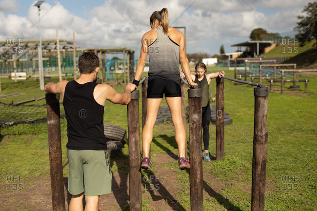 Rear view of a young Caucasian woman and a young Caucasian man using parallel bars at an outdoor gym during a bootcamp training session, with another participant facing camera in the background