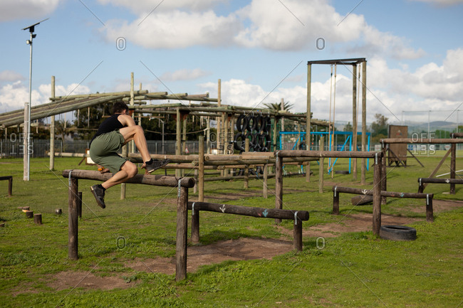 Side view of a young Caucasian man vaulting over a hurdle at an outdoor gym during a bootcamp training session