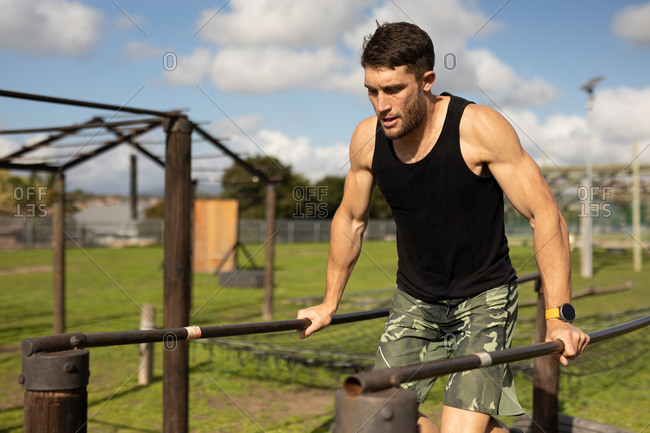 Front view close up of a young Caucasian man on parallel bars at an outdoor gym during a bootcamp training session
