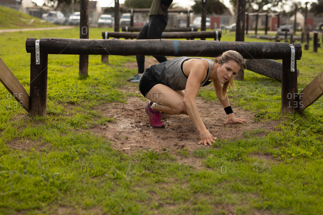 Front view of a young Caucasian woman crawling under a low hurdle at an outdoor gym during a bootcamp training session