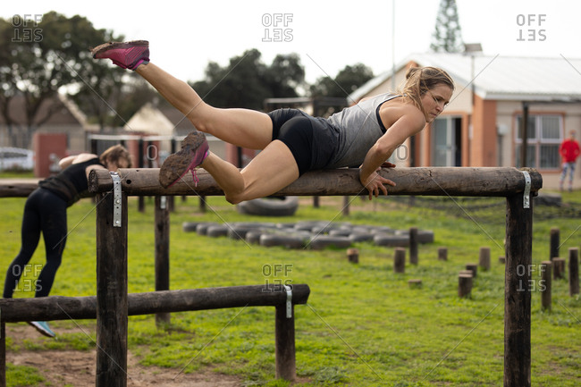 Side view of a young Caucasian woman vaulting over a hurdle at an outdoor gym during a bootcamp training session, with another participant in the background