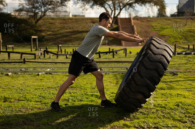 Side view of a young Caucasian man flipping a tire at an outdoor gym during a bootcamp training session