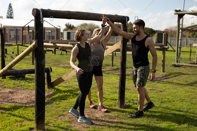 Front view of two young Caucasian women and a young Caucasian man high fiving at an outdoor gym during a bootcamp training session