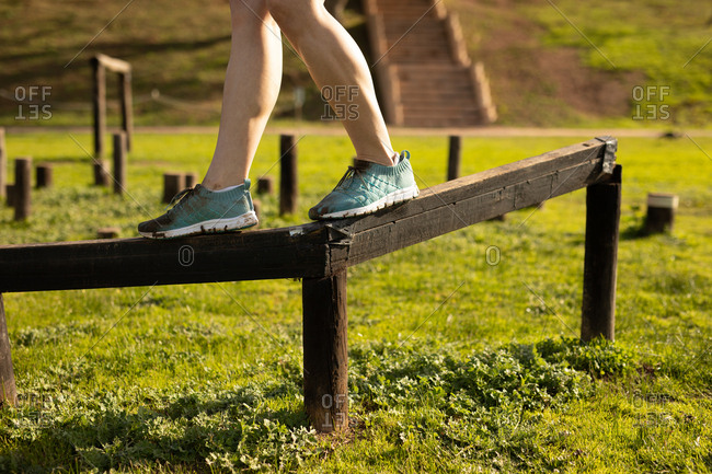 Side view low section of a young Caucasian woman walking on a beam at an outdoor gym during a bootcamp training session