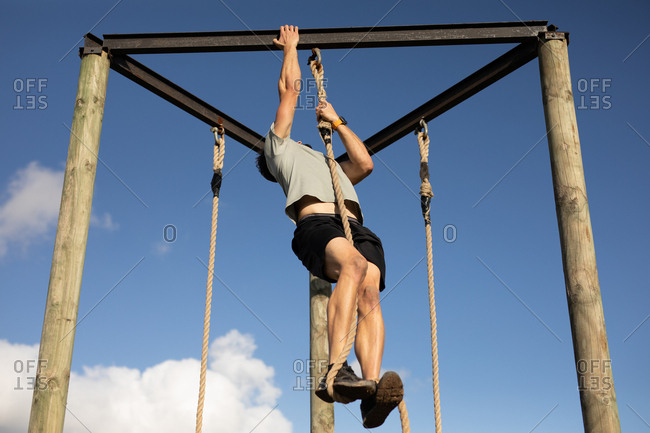 Front view of a young Caucasian man climbing a rope on a climbing frame at an outdoor gym during a bootcamp training session