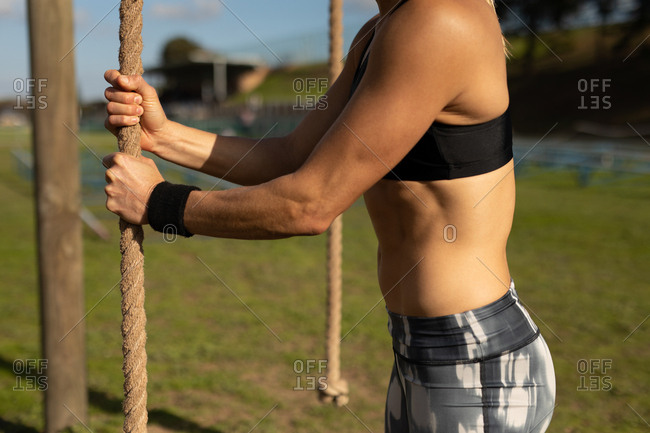 Side view mid section of a young Caucasian woman preparing to climb a rope at an outdoor gym during a bootcamp training session