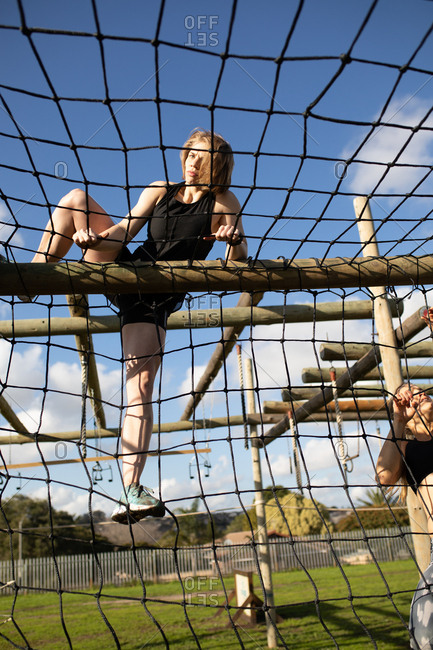 Front view close up of a young Caucasian woman climbing over nets on a climbing frame at an outdoor gym during a bootcamp training session, with another participant partly visible