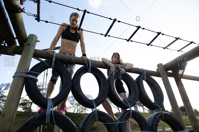 Front view of two young Caucasian women climbing over a wall of tires on a climbing frame at an outdoor gym during a bootcamp training session