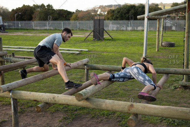 Side view of a young Caucasian woman and a young Caucasian man climbing across beams on a climbing frame at an outdoor gym during a bootcamp training session