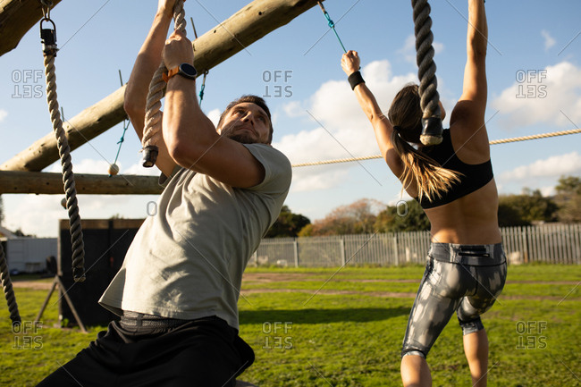 Front view close up of a young Caucasian man hanging from ropes on a climbing frame at an outdoor gym during a bootcamp training session, with a young Caucasian woman hanging from ropes in the background