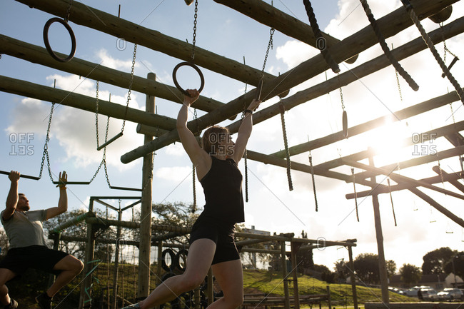 Side view of a young Caucasian woman hanging from rings on a climbing frame at an outdoor gym during a bootcamp training session, with a man climbing in the background