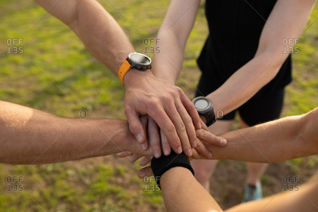 High angle low section of three young Caucasian adults standing together and stacking their hands in unity at an outdoor gym during a bootcamp training session