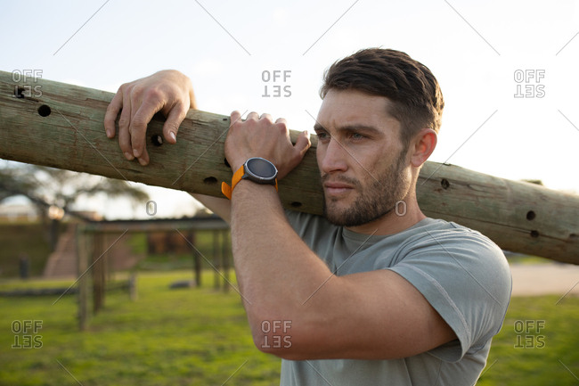 Side view of a young Caucasian man carrying a log on his shoulder at an outdoor gym during a bootcamp training session