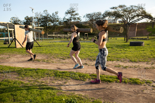 Side view of two young Caucasian women and a young Caucasian man carrying logs at an outdoor gym during a bootcamp training session