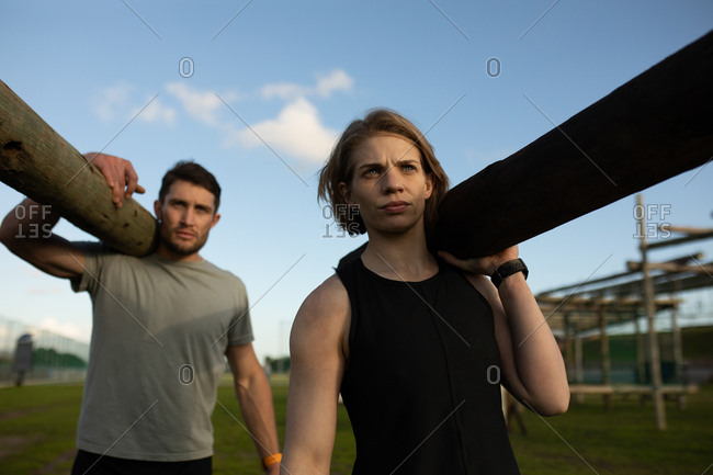 Front view of a young Caucasian woman and a young Caucasian man carrying logs of wood at an outdoor gym during a bootcamp training session