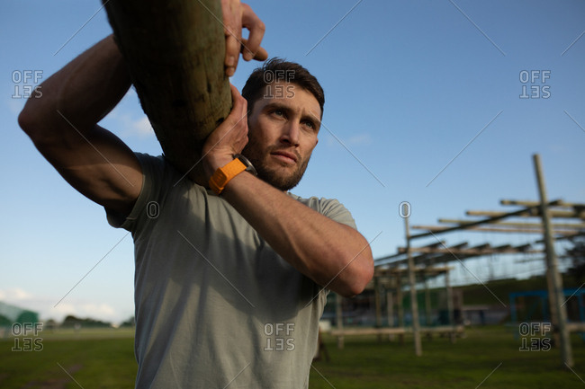Front view close up of a young Caucasian man carrying a log of wood at an outdoor gym during a bootcamp training session