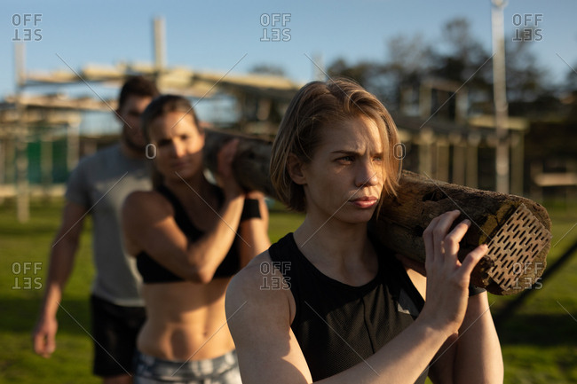 Front view of two young Caucasian women and a young Caucasian man carrying a log of wood together on their shoulders at an outdoor gym during a bootcamp training session
