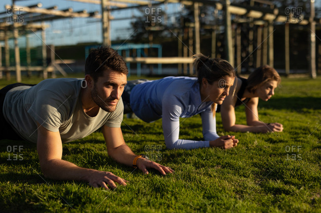Side view of two young Caucasian women and a young Caucasian man doing the plank exercise at an outdoor gym during a bootcamp training session