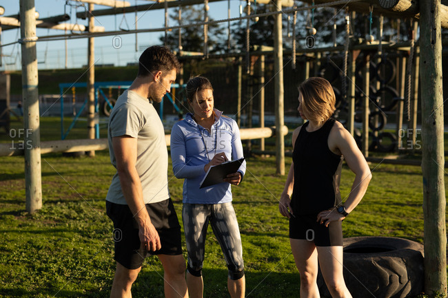 Front view of a young Caucasian woman and a young Caucasian man standing with a young Caucasian female instructor holding a clipboard during a bootcamp training session at an outdoor gym