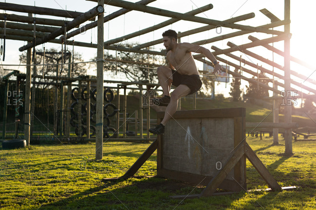 Side view of a shirtless young Caucasian man vaulting over a wall at an outdoor gym during a bootcamp training session