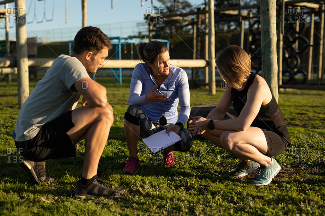 Front view of a young Caucasian woman and a young Caucasian man squatting down with a young Caucasian female trainer holding a clipboard and talking at an outdoor gym during a bootcamp training session