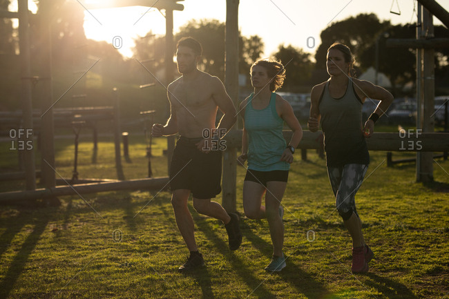 Front view of two young Caucasian women and a young Caucasian man running at an outdoor gym during a bootcamp training session, backlit by sunlight