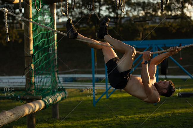 Side view of a shirtless young Caucasian man  hanging from a horizontal rope on a climbing frame at an outdoor gym during a bootcamp training session